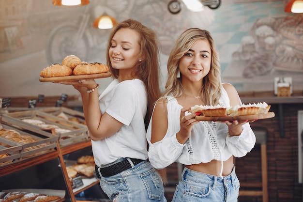 Красивые девушки покупают булочки в пекарне