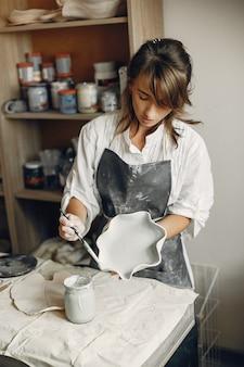 若い女性はワークショップで陶器を作る