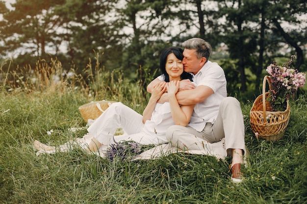 美しい大人のカップルが夏の畑で時間を過ごす