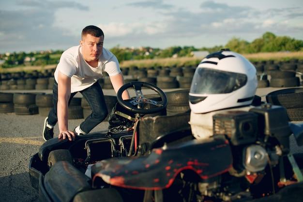 Красивый мужчина в картинге с автомобилем