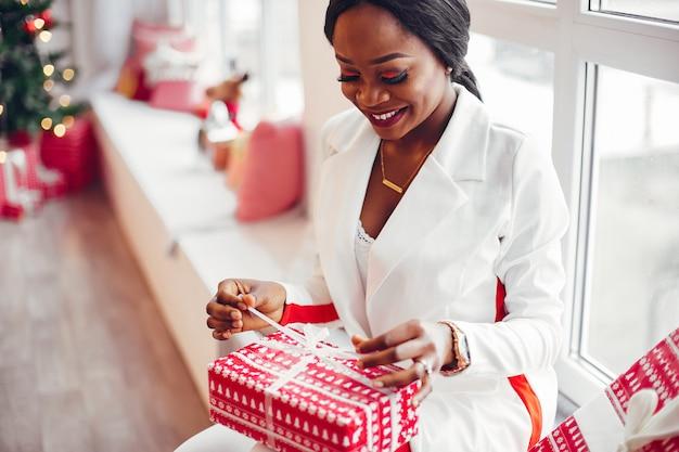Элегантная черная девушка в комнате на рождество
