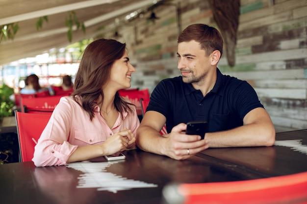 Красивая пара, сидя в летнем кафе