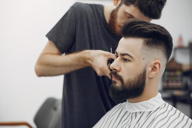 Стильный мужчина сидит в парикмахерской