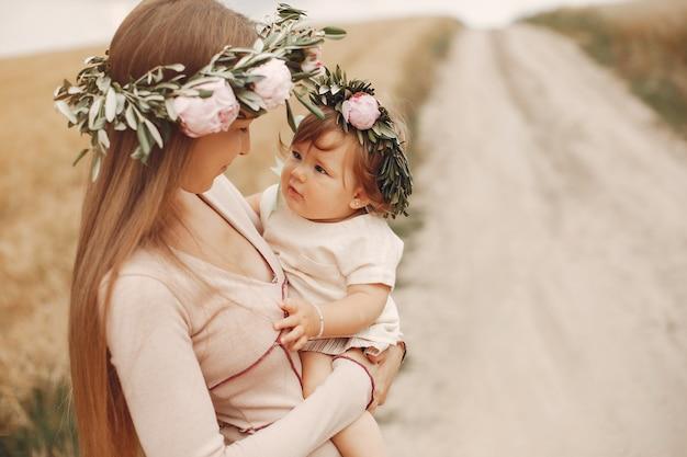 夏の畑で遊ぶ娘を持つ母