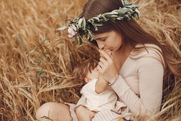 フィールドでかわいい小さな娘とエレガントな母