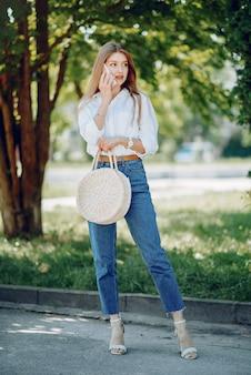 Элегантная блондинка в летнем парке с телефоном