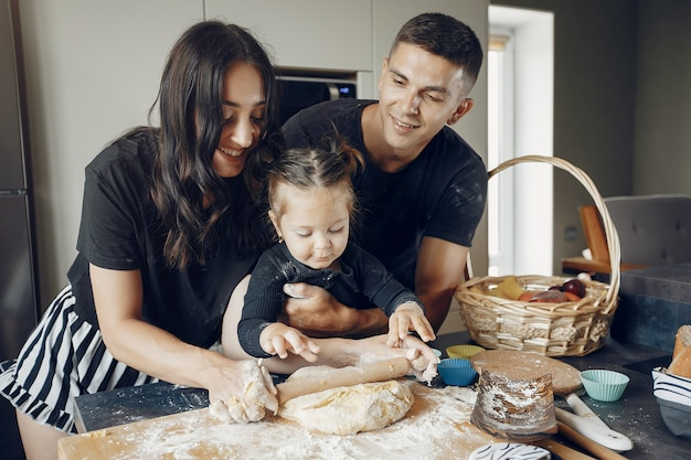 Семья готовит тесто для печенья на кухне