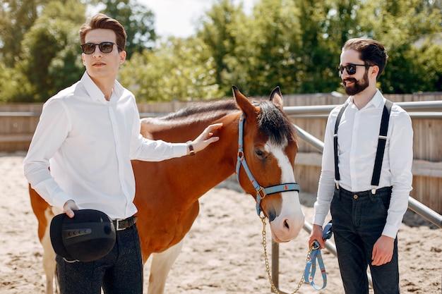 牧場で馬の隣に立っているエレガントな男性