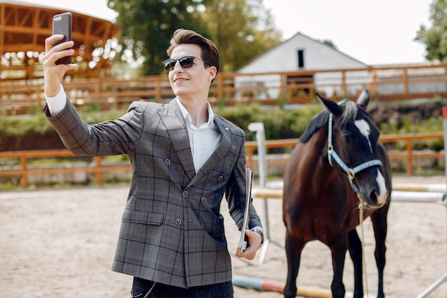 牧場で馬の隣に立っているエレガントな男