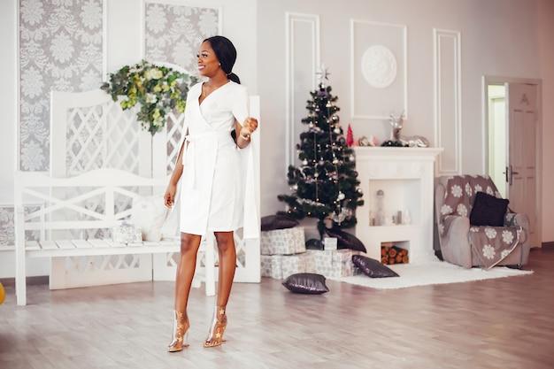 Элегантная черная девушка в украшенной рождеством комнате