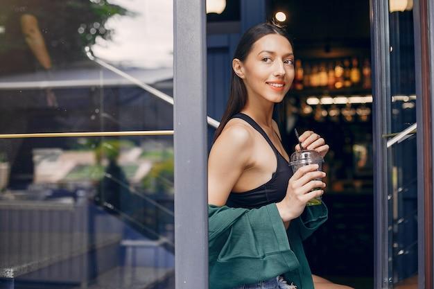 夏のカフェに立っているファッションの女の子