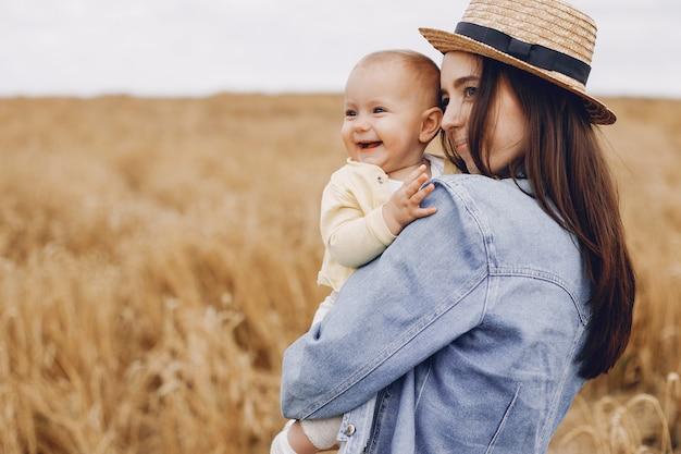 秋のフィールドで遊ぶ娘を持つ母