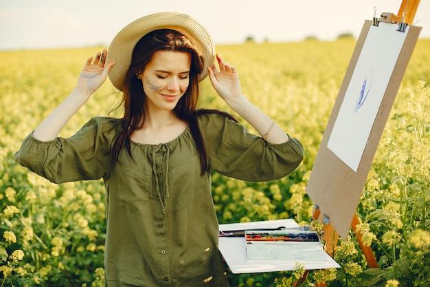 Элегантная и красивая девушка рисует в поле