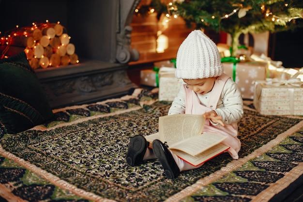 座っているクリスマスツリーの近くの小さな女の子