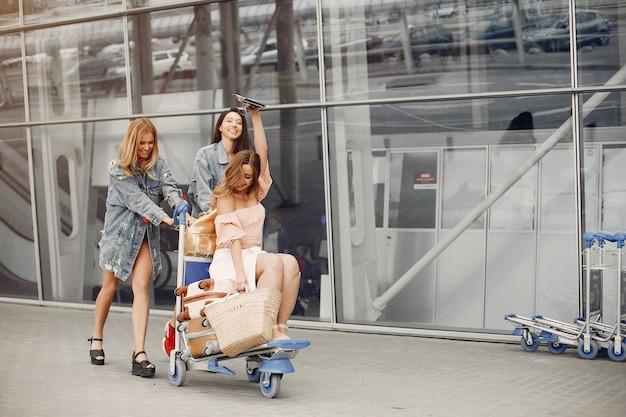 Три красивые девушки стоят у аэропорта