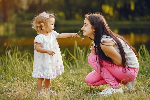 夏の公園で遊ぶ娘を持つ母