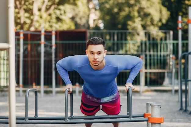 Красивый мужчина, обучение в парке летом