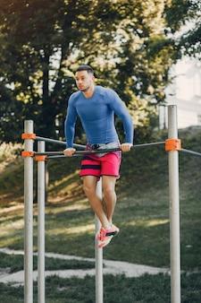 ハンサムな男が夏の公園でトレーニング