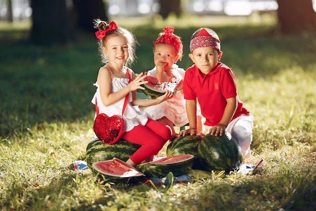 公園でスイカとかわいい小さな子供たち
