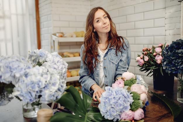 Флорист в цветочном магазине делает букет
