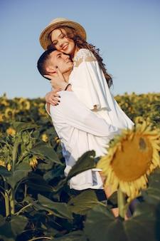 Красивая и стильная пара в поле с подсолнухами