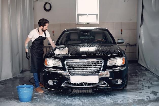 ガレージで彼の車を洗う人