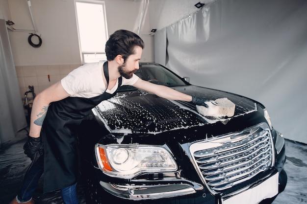 Мужчина моет машину в гараже