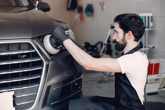 Человек полирует машину в гараже