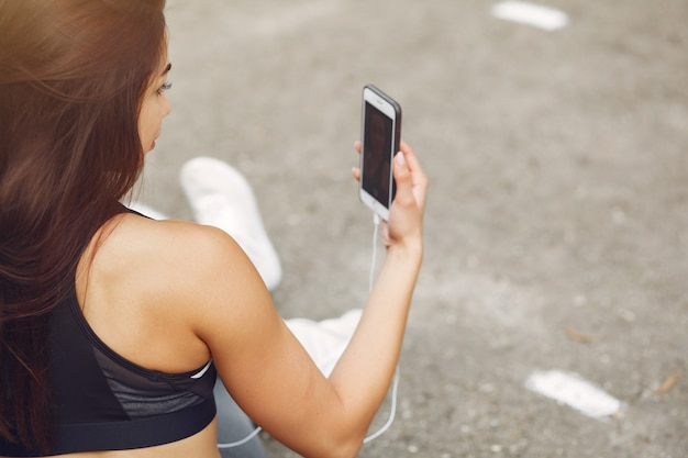 Спортивная тренировка девушки с телефоном и наушниками