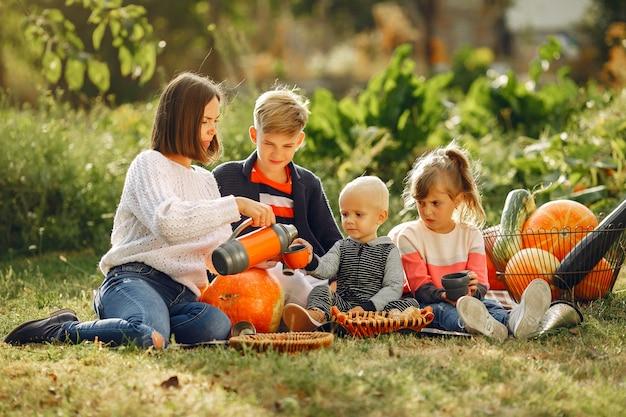 Большая семья сидит в саду возле многих тыкв