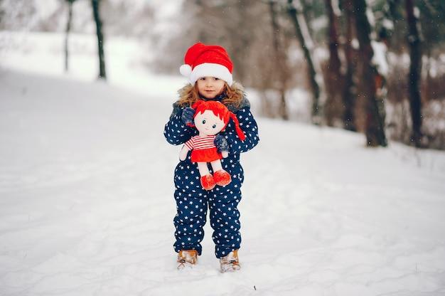 冬の森で遊ぶ青い帽子の少女