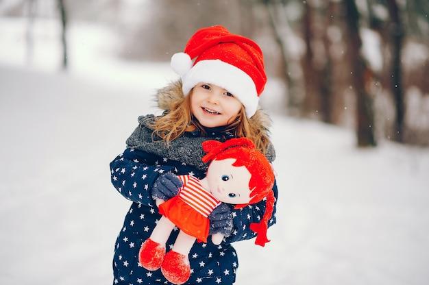 Маленькая девочка в синей шляпе играет в зимнем лесу