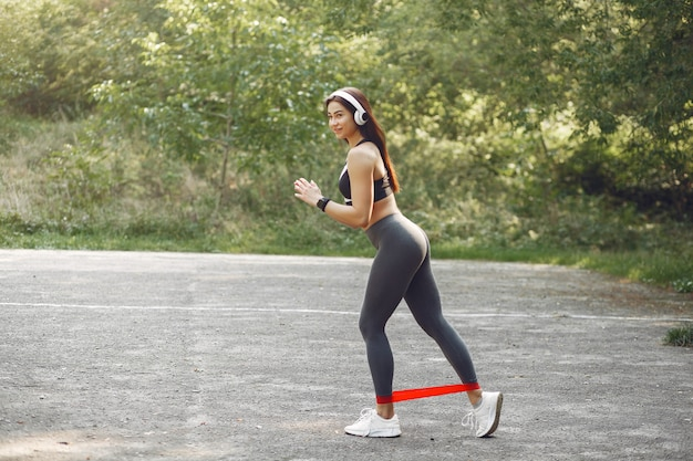 Спортивная тренировка девушки со спортивными резинками
