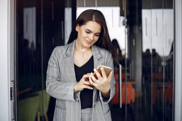 Элегантная коммерсантка работая в офисе и использует телефон