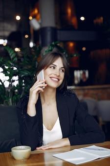 Деловая женщина сидит за столом в кафе и работает