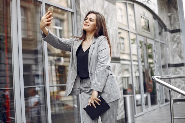 Элегантная коммерсантка работая в городе и использует тетрадь
