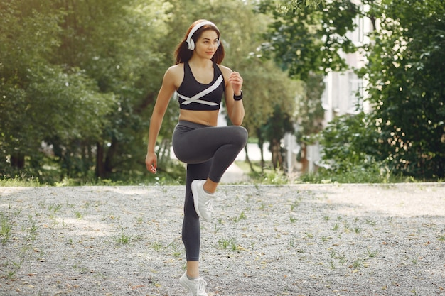 Спортивная тренировка девушки с наушниками в летнем парке