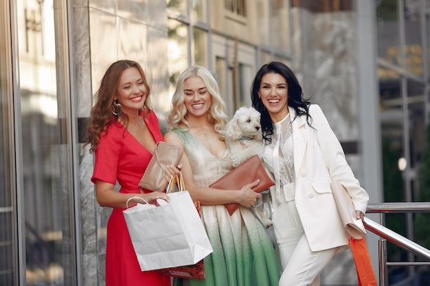 Три элегантные женщины с сумками в городе