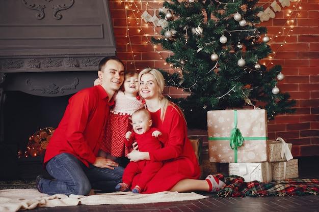 クリスマスツリーの近くに家で座っている家族