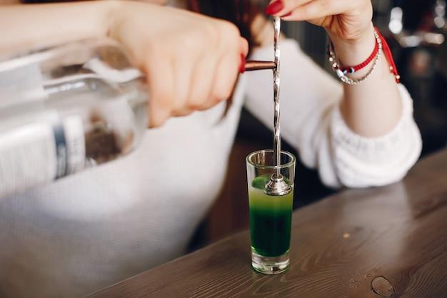 ガラスに緑のシロップを注ぐ白いセーターの女性