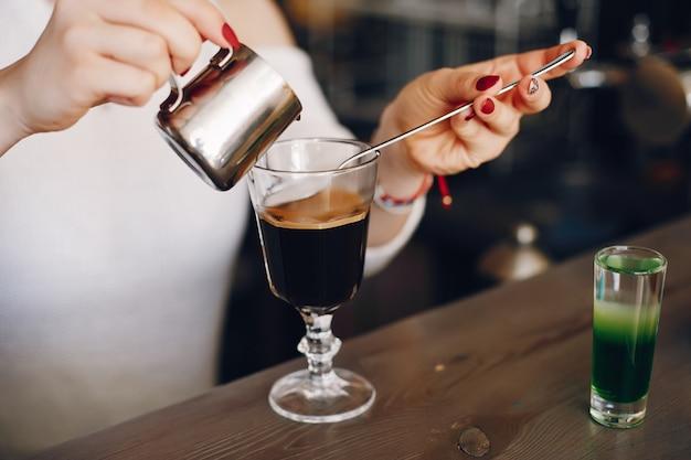 コーヒーデザートにミルクを注ぐ白いセーターの女性