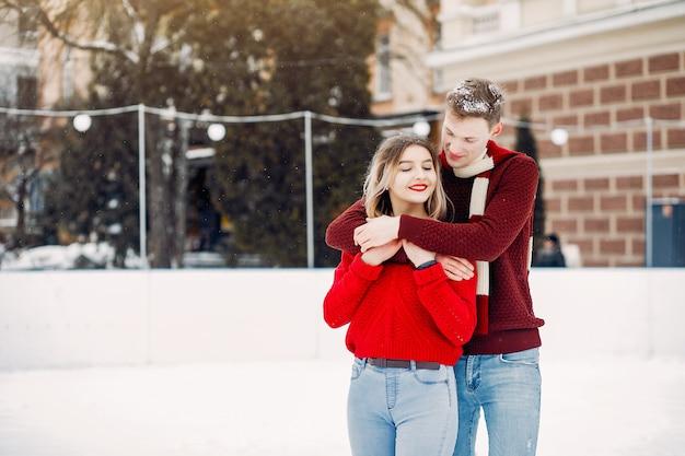 冬の街で赤いセーターを着たキュートで愛情のあるカップル
