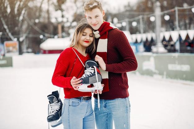 Милая пара в красных свитерах развлекается на ледовой арене