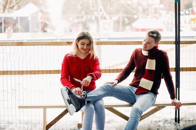 Милая пара в красных свитерах помогает друг другу кататься на коньках