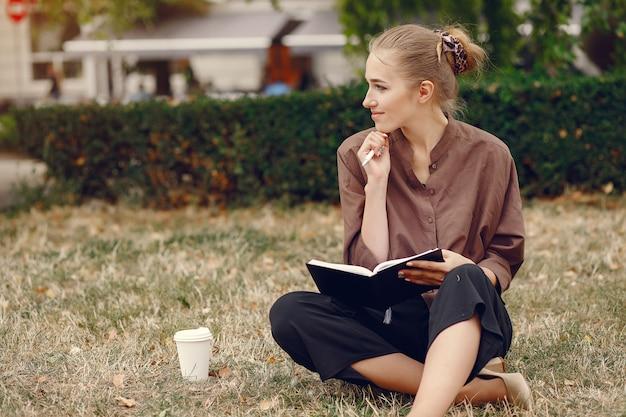 公園で働くかわいい学生とノートを使用