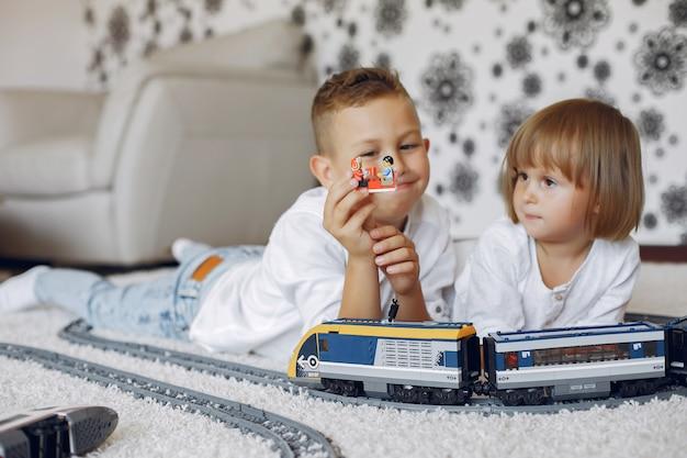 Дети играют с лего и игрушечным поездом в игровой комнате