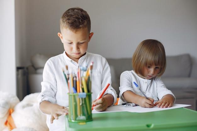 緑のテーブルに座って、図面の子供たち