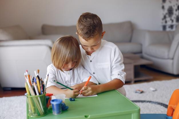 Дети сидят за зеленым столом и рисуют