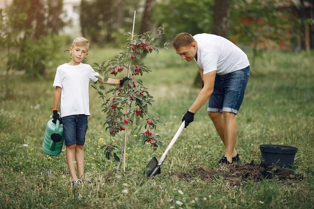 幼い息子を持つ父は庭に木を植えています