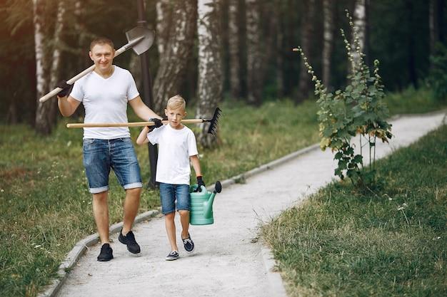 幼い息子を持つ父は公園で木を植えています